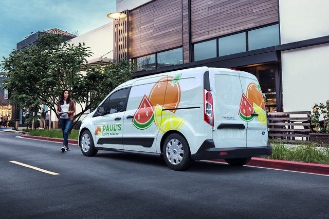 2020 Ford Transit connect Cargo Van with business graphics parked on city street
