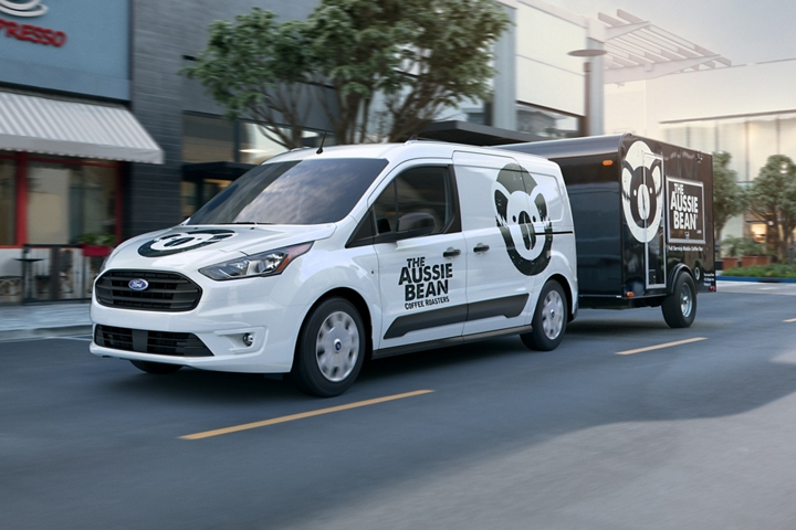 2020 Ford Transit Connect Cargo Van in Frozen White with business graphics towing a trailer in the city