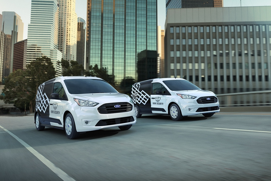 Two 2020 Ford transit connect cargo vans with aftermarket business graphics take to the road