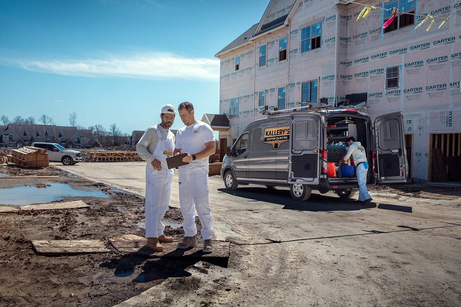 Construction workers on a large scale site looking at a tablet with a 2020 Ford Transit in Iconic Silver in the background