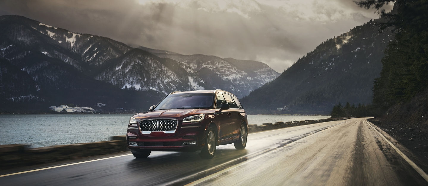Lincoln Aviator is shown driving past a lake on a mountain road