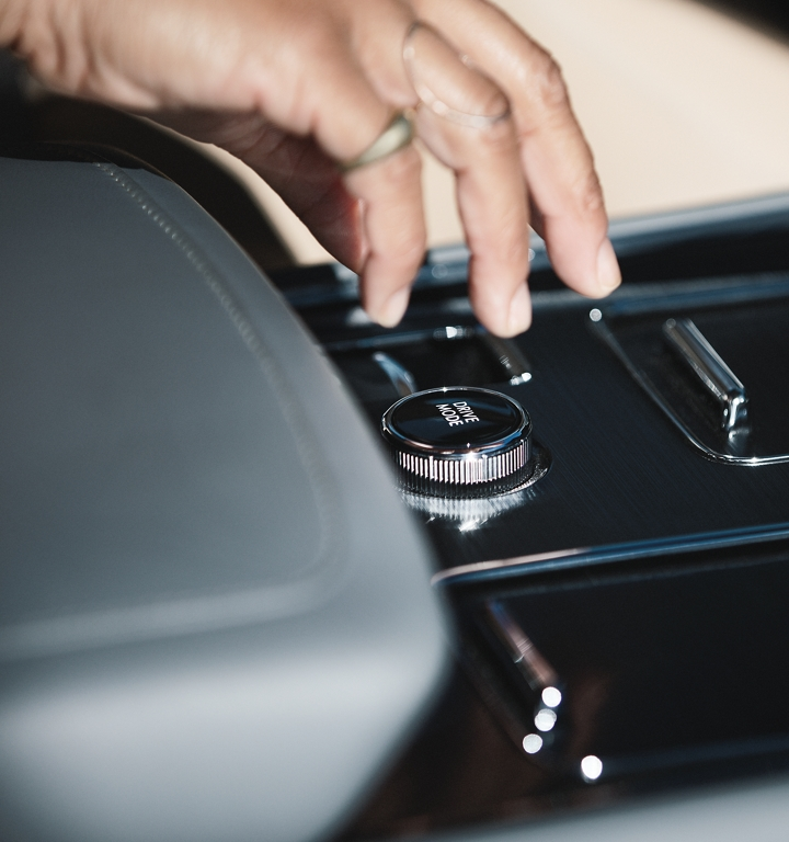 A hand is shown reaching for the knob that helps drivers easily switch between up to 7 unique drive modes