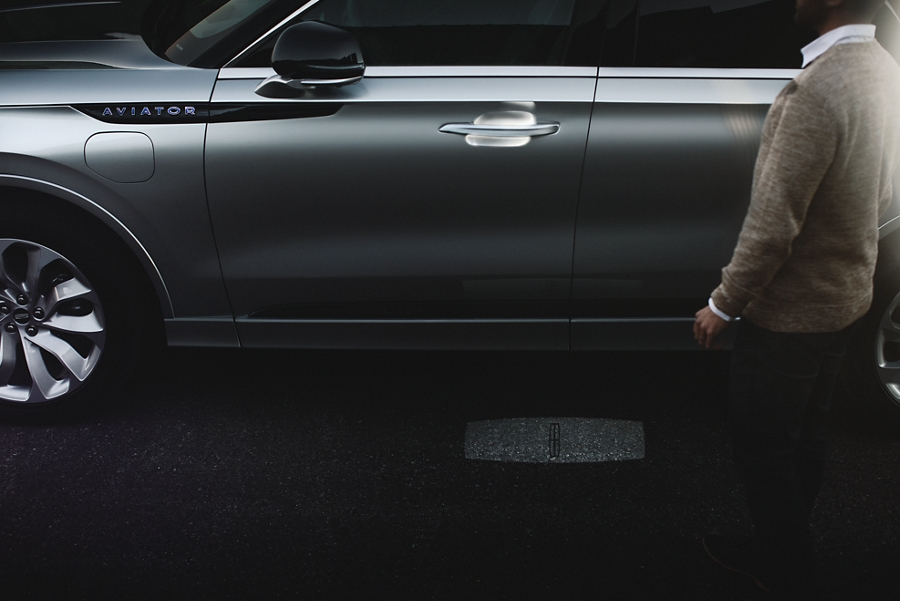 A person is shown approaching a Lincoln Aviator as an illuminated welcome mat is project on the ground