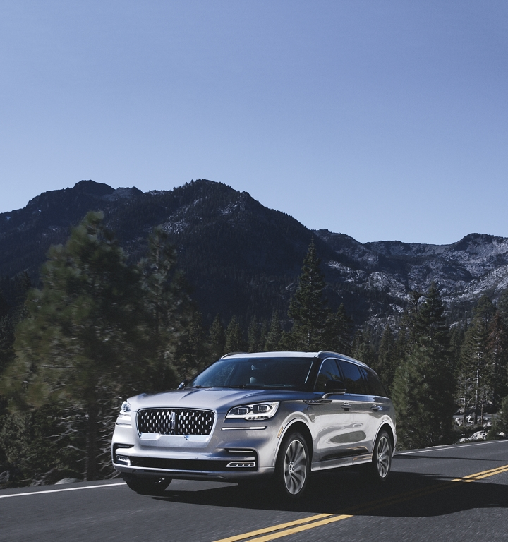 A Lincoln Aviator Grand Touring is shown being driven along a winding mountain road