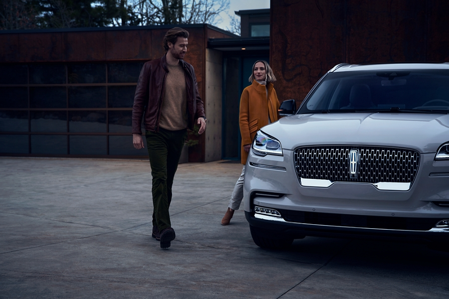 A couple is shown approaching a Lincoln Aviator in the driveway of a modern home