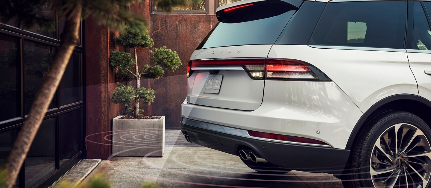 A Lincoln Aviator is shown utilizing the reverse brake assist feature in a driveway