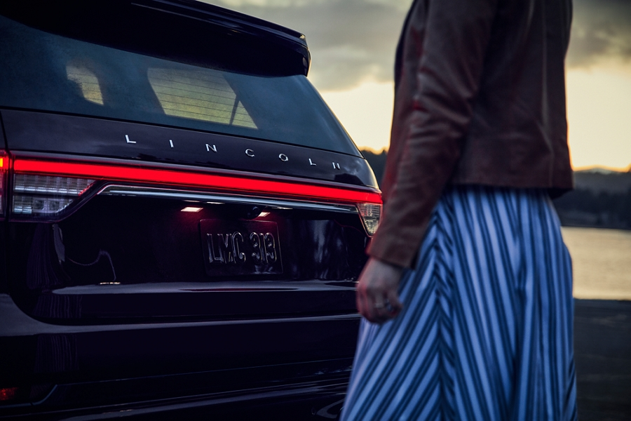 A woman is seen approaching the rear of a Lincoln Aviator which have illuminated as part of the Lincoln Embrace experience