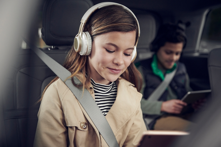 Two children are shown in the second and third row of a Lincoln Aviator as they use 4 G Wi-Fi