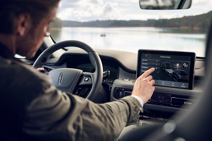 The driver in a parked Lincoln Aviator is shown adjusting the intelligent adaptive cruise control settings in the centre touch screen
