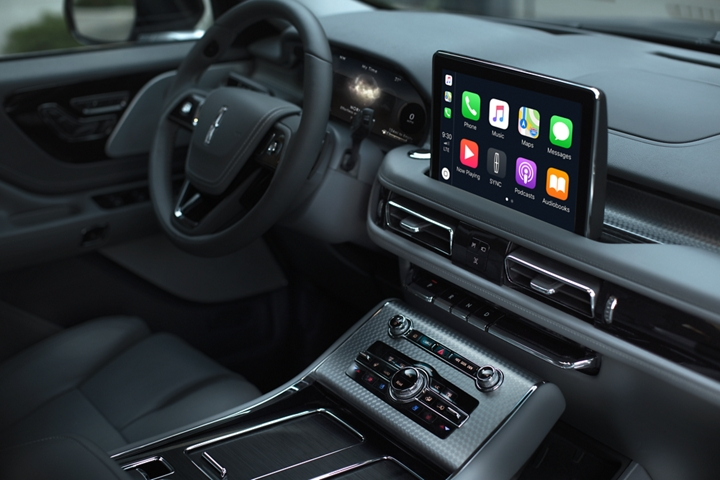 The centre console touch screen is shown displaying a number of smart phone compatible capabilities