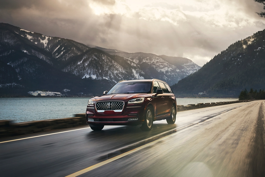 A Lincoln Aviator Grand Touring in the Burgundy velvet exterior colour is shown being driven on a breathtaking river valley road