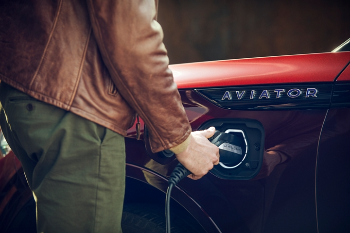 A hand is shown easily using the at home charging station that helps to power the Lincoln Aviator Grand Touring model