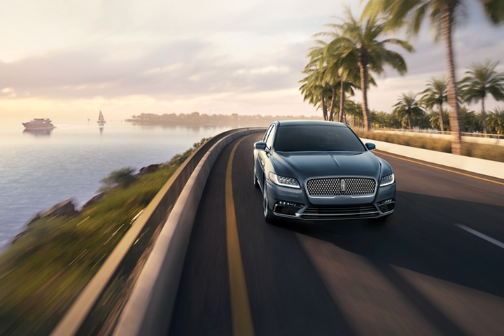 A fast moving Lincoln Continental demonstrates its agility on a turn on a coastal highway