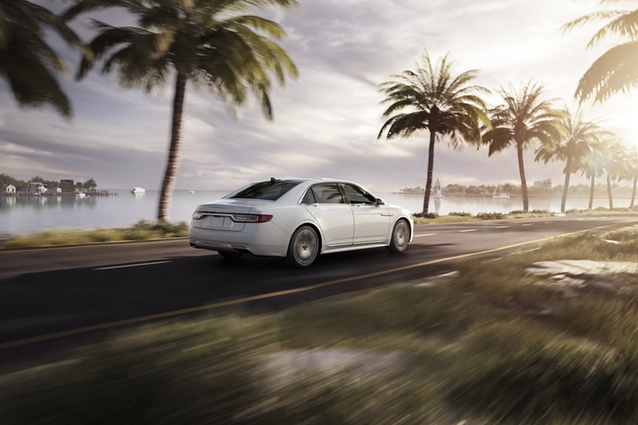 The Lincoln Continental shown in White Platinum is being driven toward a warm sunset