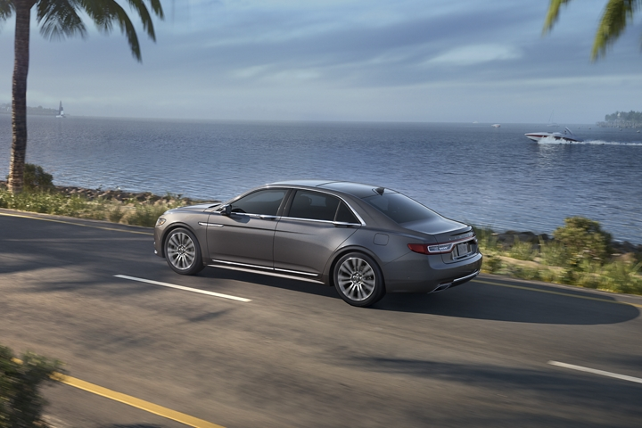 The Lincoln Continental shown in Magnetic Grey is being driven along a coastline