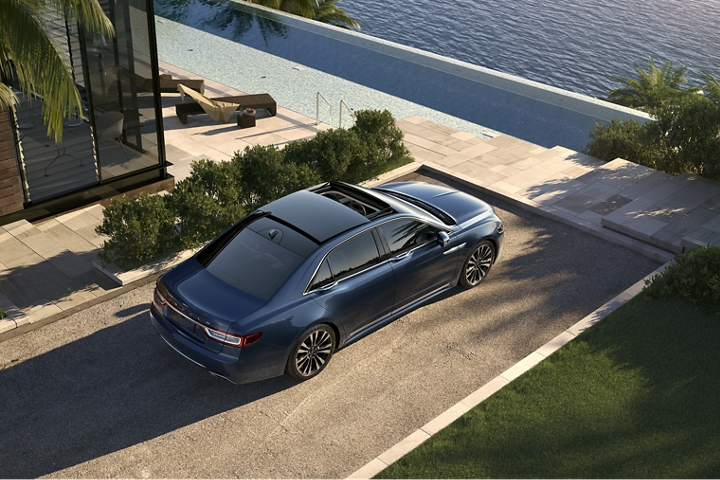 The Lincoln Continental in Blue Diamond parked in the driveway of an elegant shoreline home