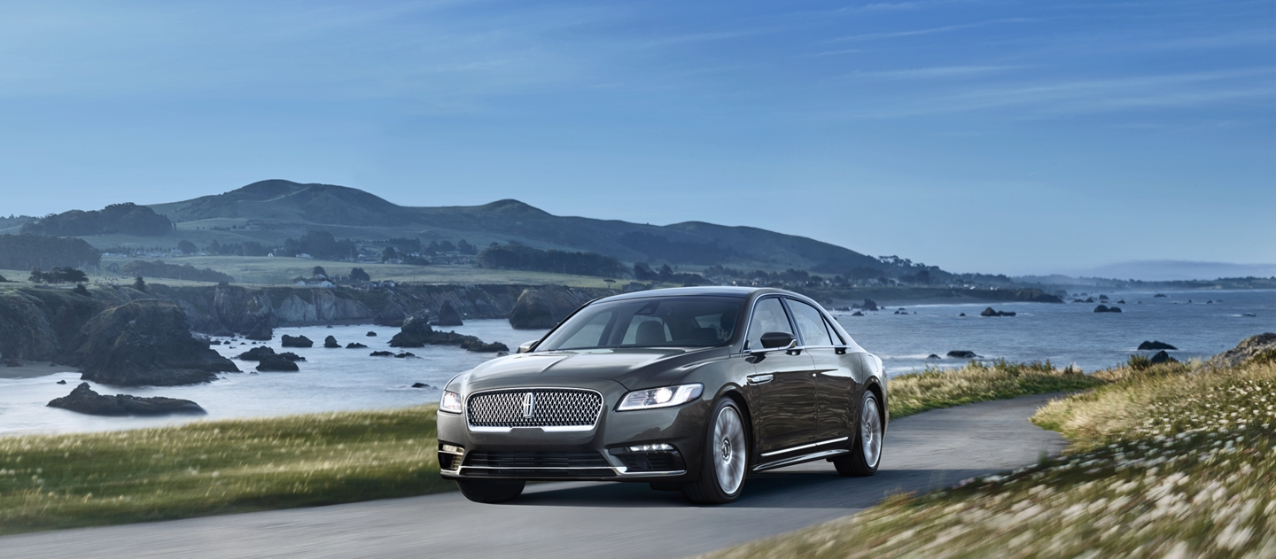 A Lincoln Continental is shown being driven on a road that follows an ocean coastline