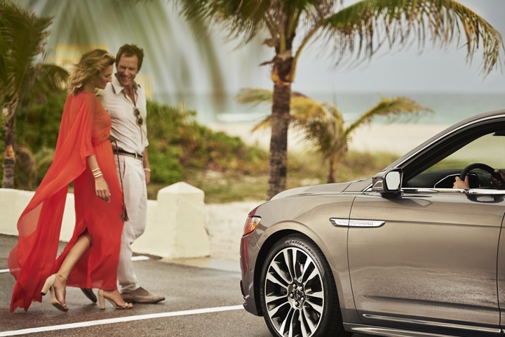 A couple is shown using a pedestrian crossing in front of a 2020 Lincoln Continental