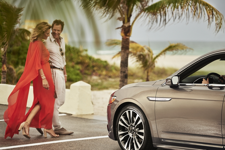 A couple uses a pedestrian crossing in front of the 2020 Lincoln Continental