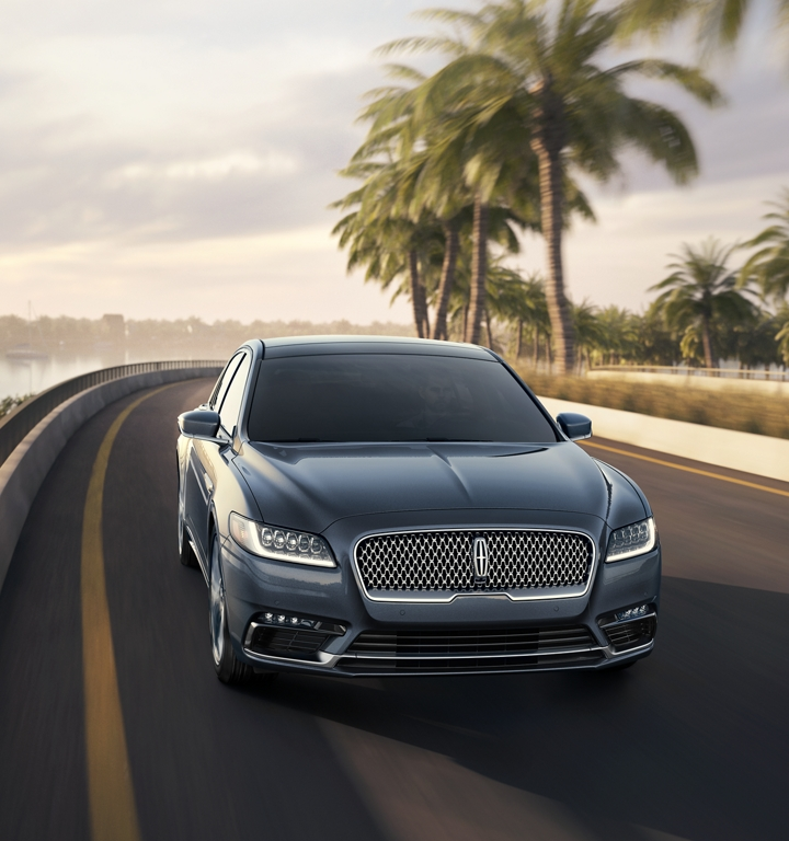 An impressive look at the front grille of a fast moving 2020 Lincoln Continental on a coastal highway