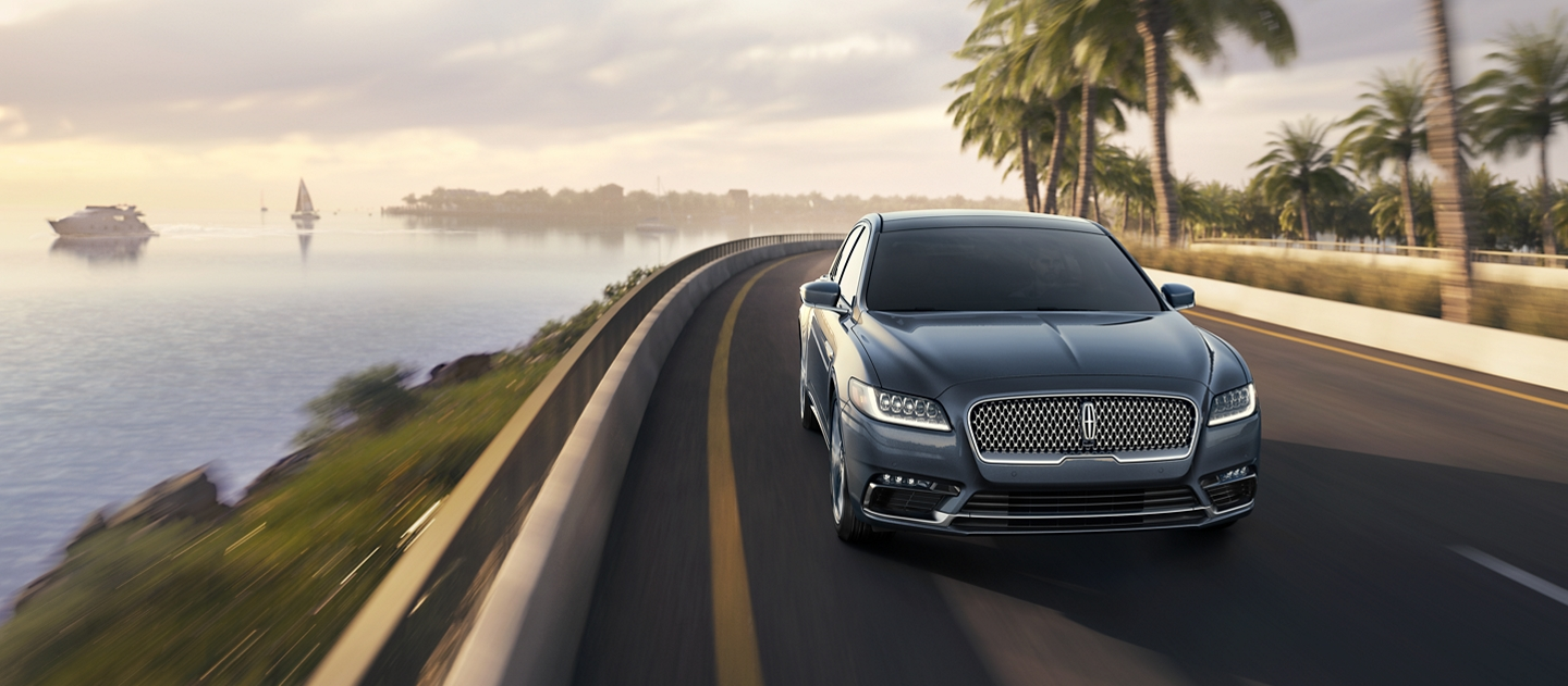 A 2020 Lincoln Continental is shown being driven up a steep rain slicked hill to demonstrate the capabilities of intelligent all wheel drive