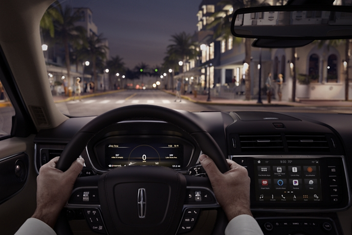 A city scene with pedestrians in the distance is shown through the windshield of a 2020 Lincoln Continental