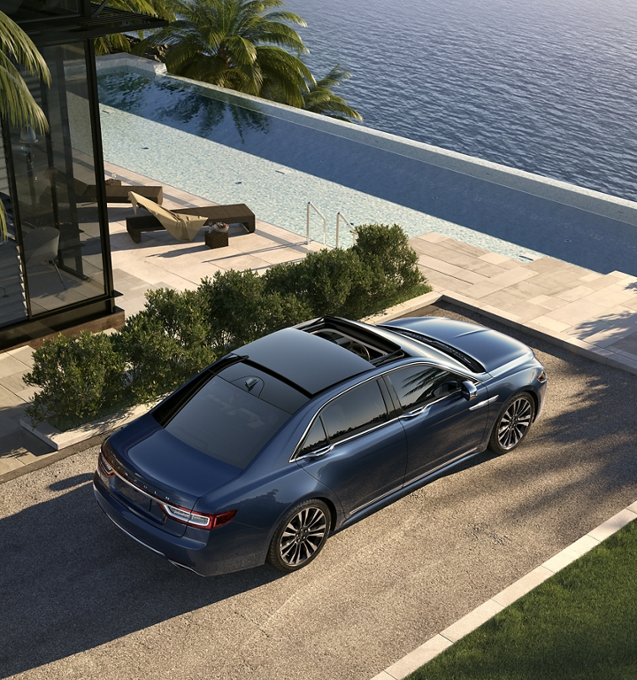 The 2020 Lincoln Continental is shown parked at an inviting waterfront home while it shows off its available retractable moonroof