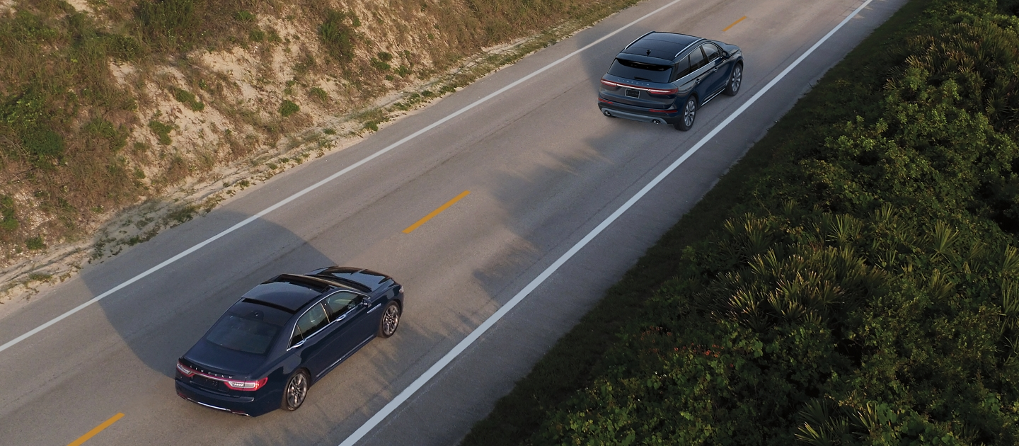 A 2020 Lincoln Continental is shown being driven on a road as it approaches another vehicle to demonstrate the capabilities of pre collision assist