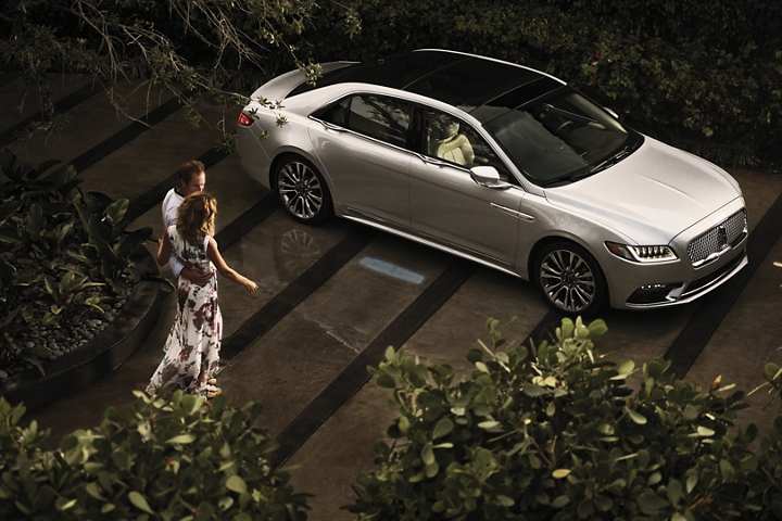 A splash of light is projected on the ground from the 2020 Lincoln Continental to help guide a couple as they approach