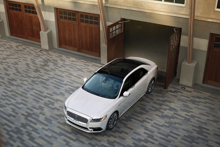 A 2020 Lincoln Continental is shown emerging from a garage with stately double carriage doors