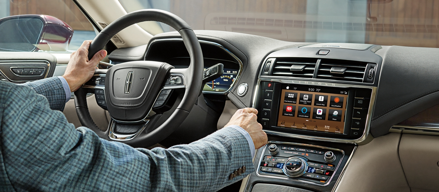 The driver of a 2020 Lincoln Continental is shown reaching for the centre touch screen to demonstrate the WiFi capability