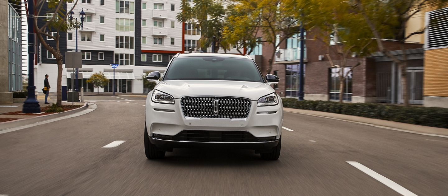 A 2020 Lincoln Corsair in pristine white is being driven through an urban setting with responsive performance