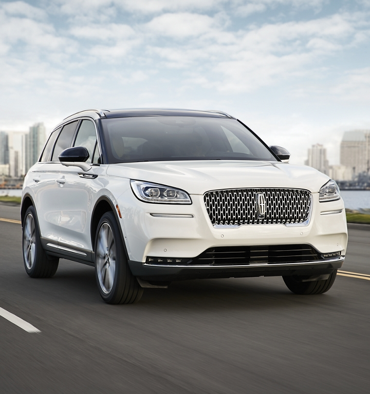 A 2020 Lincoln Corsair in pristine white is effortlessly being driven along a coast using Lincoln Drive modes