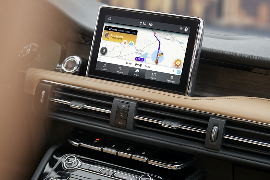 The centre screen of a cashew interior is running the Waze navigation app on a broad digital display
