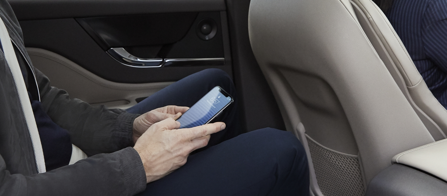 A rear seat passenger in a sandstone interior enjoys the convenient four G L T E wi fi hotspot on his smartphone device