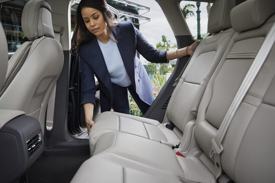 A woman slides the second row seat forward to create more cargo space in the trunk