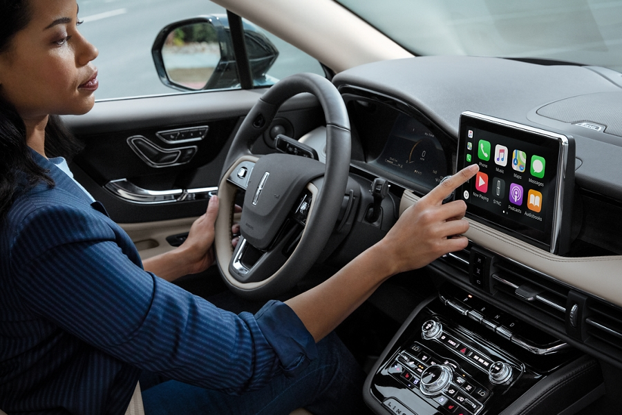A woman in the drivers seat of a 2020 Lincoln Corsair is touching the centre digital screen to connect to Apple Carplay