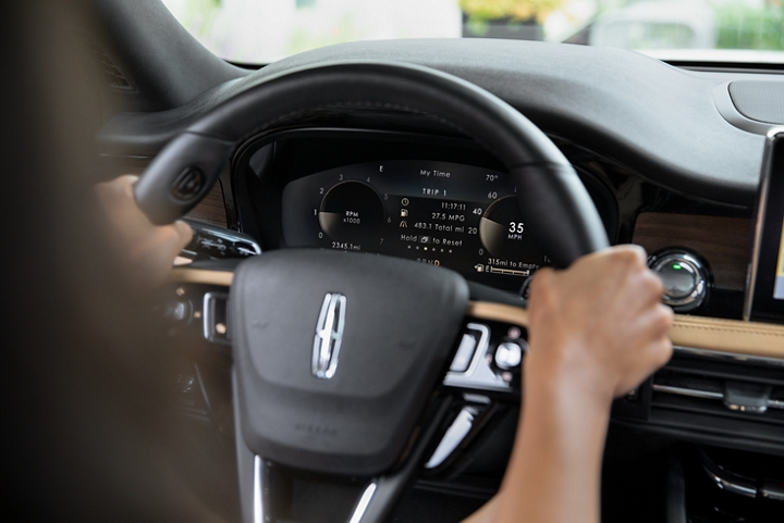 A friendly considerate prompt alert is displayed in the digital cluster behind the steering wheel inside a Lincoln Corsair