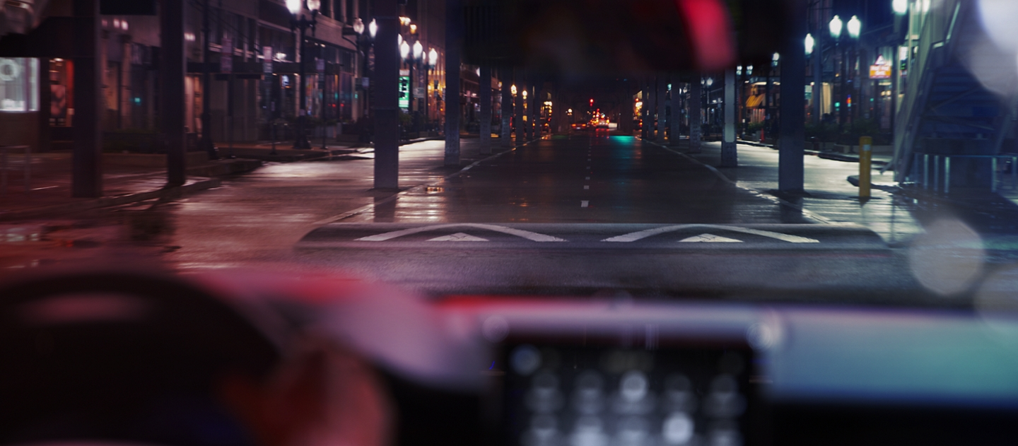 Through the windshield of a 2020 Lincoln Corsair is a downtown intersection with a pedestrian crosswalk speed hump ahead