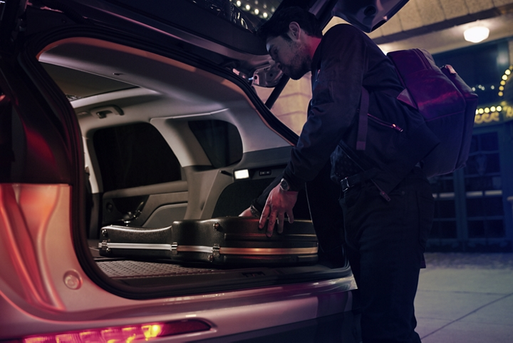 A musician slides his guitar case into the cargo space of a Lincoln Corsair with the rear seats folded flat to provide ample cargo space