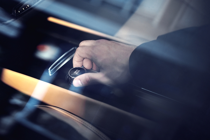 Through an exterior window reflecting surrounding skyscrapers we see a drivers hand turning the Lincoln drive modes knob near the centre console