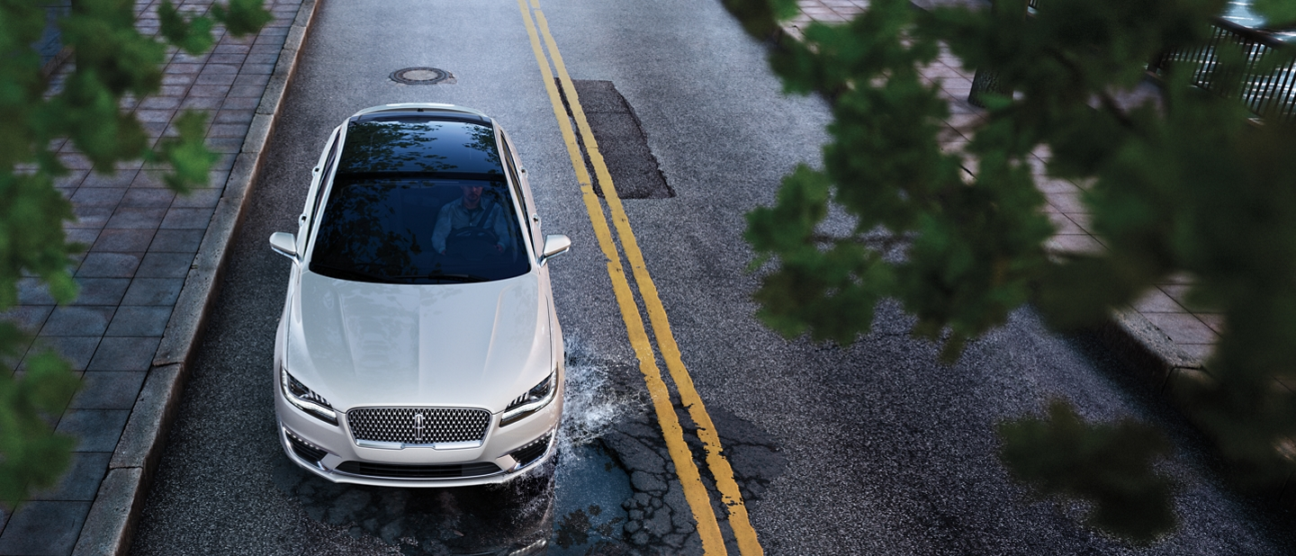 A 2020 Lincoln M K Z is seen being driven toward a larger pothole to demonstrate the adaptive suspension