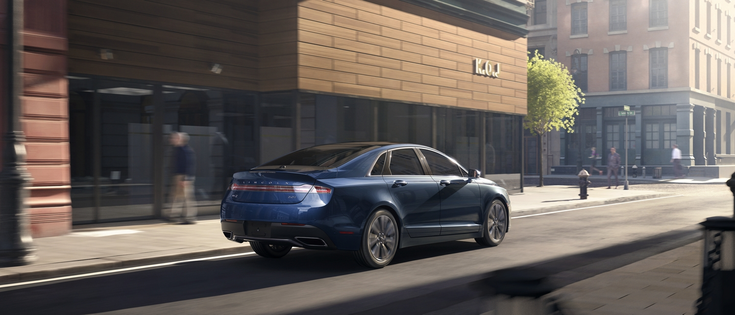 A 2020 Lincoln M K Z is shown being driven through an urban setting with a number of pedestrians on nearby sidewalks