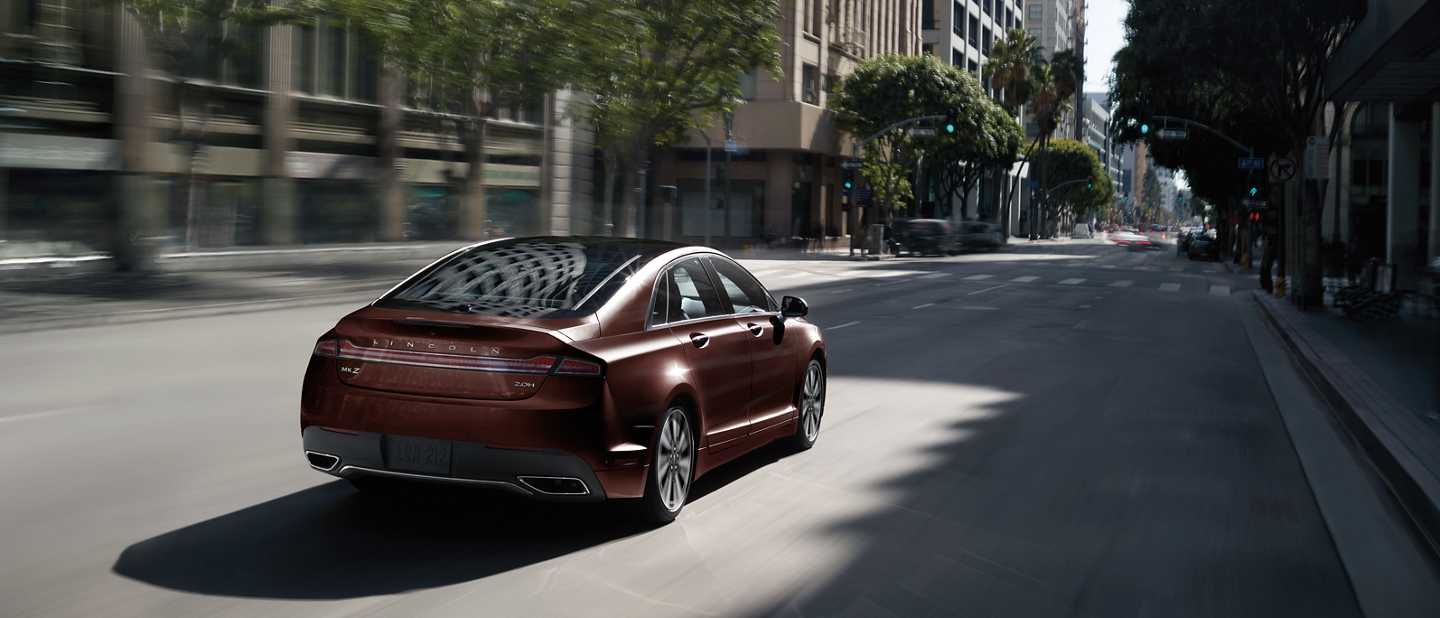A 2020 Lincoln M K Z is shown being driven in an urban setting on a street lined with trees