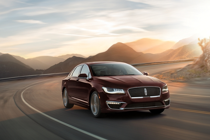 A 2020 Lincoln M K Z shown in Magma Red Metallic Clearcoat is being driven on a sharp mountain turn