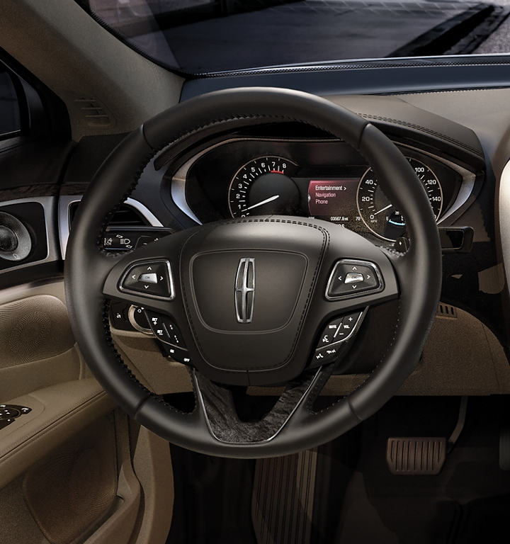 The leather steering wheel in the 2020 Lincoln M K Z is shown with sunlight bouncing off the in wheel controls
