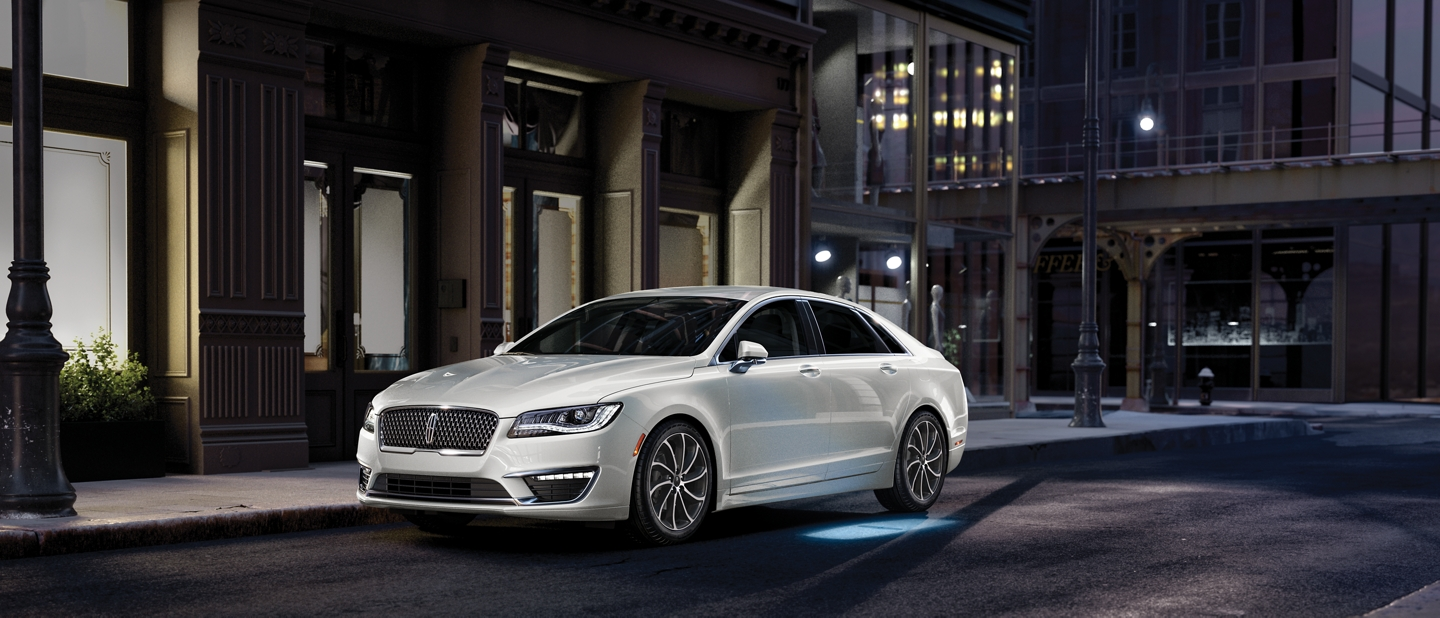 A 2020 Lincoln M K Z is shown parked in a city setting at night while a welcome mat of light is projected onto the ground from the vehicle