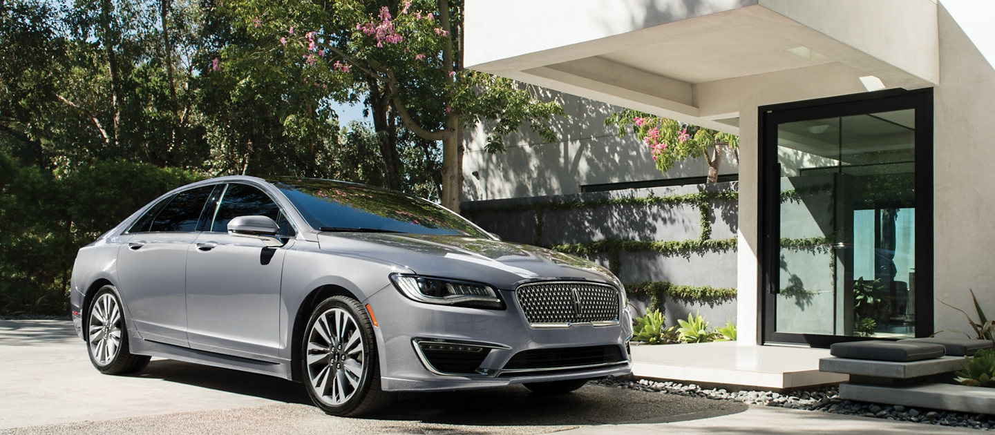 A 2020 Lincoln M K Z in Silver Radiance Metallic Clearcoat is shown parked next to the entrance of a modern home