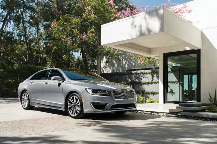 A 2020 Lincoln M K Z in the Silver Radiance Metallic Clearcoat exterior colour is shown parked next to the entrance of a modern home