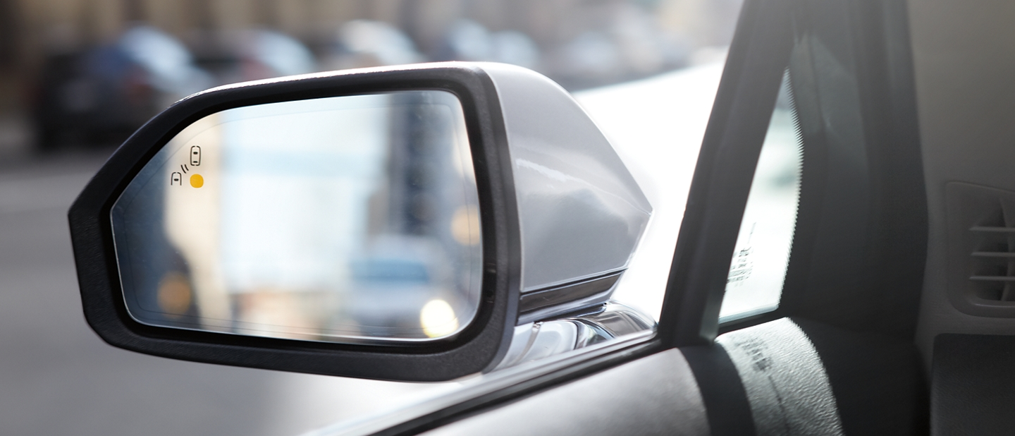 The sideview mirror of a 2020 Lincoln M K Z is shown displaying a warning indicating that another vehicle is in the blind spot